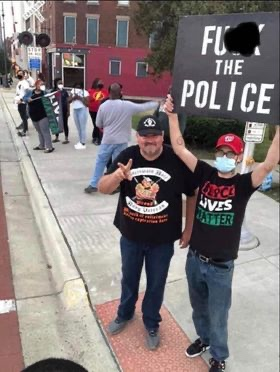 Joedy Brown, Veteran, Wife, Mother, and Mayoral Candidate's Son is not holding a F*** the Police Sign while his father is throwing a Peace sign.