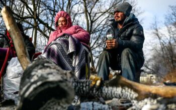 © Nick King/Lansing State Journal William File and Heather Vincent warm themselves by a fire at a homeless encampment on Wednesday, Dec. 9, 2020, in Lansing.